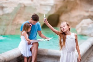 Family with touristic map near Fontana di Trevi, Rome, Italy. Little girl with toy airplane background of Trevi Fountain. Happy father and kids enjoy italian vacation holiday in Europe.