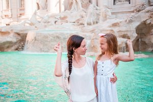Travel family mom and girl trowing coin at Trevi Fountain, Rome, Italy for good luck. Happy family enjoy their italian vacation holiday in Europe. Little girl making a wish to come back.