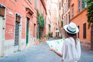 Happy young woman with a city map on desert street in Europe. Travel tourist woman with map in Rome outdoors during holidays in Italy.