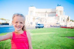 Adorable little girl taking selfie in front of Altare della Patria, Monumento Nazionale a Vittorio Emanuele II also known as II Vittoriano, Rome, Italy.