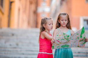 Adorable little girl looking at touristic map in roman streets in Italy. Happy toodler kids enjoy italian vacation holiday in Europe.