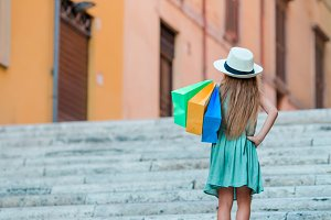 Adorable little girl walking with shopping bags outdoors in Rome. Fashion toddler kid in Italian city with her shopping