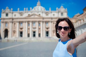 Happy young woman taking selfie at St. Peter's Basilica church in Vatican city, Rome. Beautiful caucasian tourist making selfie photo picture on european vacation in Italy.