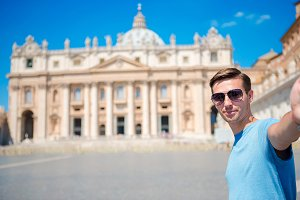 Young man taking selfie background St. Peter's Basilica church in Vatican city, Rome. Caucasian tourist making selfie photo picture on european vacation in Italy.