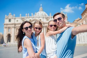Happy young family taking selfie at St. Peter's Basilica church in Vatican city, Rome. Happy travel parents and kids making selfie photo picture on european vacation in Italy.