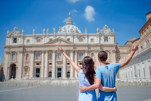 Happy couple tourists looking at St. Peter's Basilica church in Vatican city, Rome, Italy. The St. Peter's Basilica church in Vatican city is the main tourist attractions of Rome.