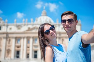 Happy couple tourists taking selfie background St. Peter's Basilica church in Vatican city, Rome, Italy. The St. Peter's Basilica church in Vatican city is the main tourist attractions of Rome.