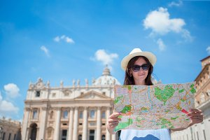 Happy young woman with city map in Vatican city and St. Peter's Basilica church, Rome, Italy. Travel tourist woman with map outdoors during holidays in Europe.