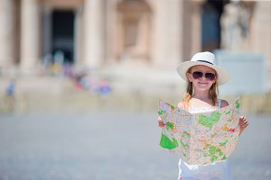 Adorable little girl with touristic map in St. Peter's Basilica square, Italy. Happy toodler kid enjoy italian vacation holiday in Europe.