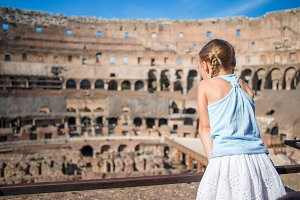 Little girl in Coliseum, Rome, Italy. Back view of kid looking at famous places in Europe