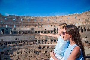 Family exploring Coliseum inside in Rome, Italy. Mother and her daughter portrait at famous places in Europe