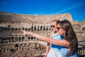 Young mother and little girl hugging in Coliseum, Rome, Italy. Family portrait at famous places in Europe