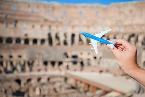 Closeup toy airplane inside on Colosseum background. Italian european vacation in Rome. Concept of travel imagination.