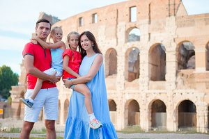 Happy family in Rome over Coliseum background. Italian european vacation together