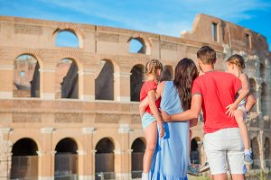 Happy family of four enjoy italian vacation on Colosseum background. Italian european family vacation in Rome