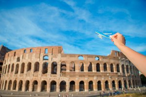 Closeup toy airplane on Colosseum background. Italian european vacation in Rome. Concept of travel imagination.