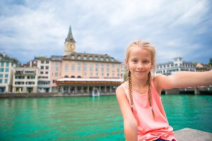 Adorable little girl taking selfie with mobile phone outdoors in Zurich, Switzerland. Closeup portrait of beautiful kid background of cute city