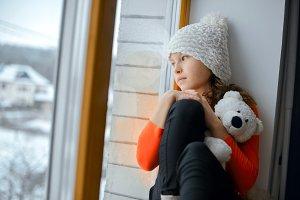 Cute girl with long hair sitting alone near window on  a windowsill
