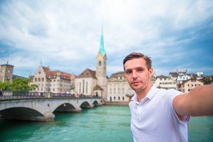 Young man taking selfie background famous Fraumunster Church and river Limmat, Switzerland.