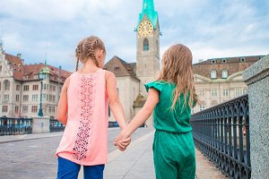 Adorable fashion little girls outdoors in Zurich, Switzerland. Two kids walking together in european city.