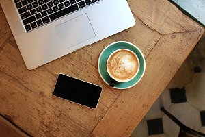 Cup of coffee on table with phone