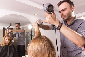 man hairstylist drying woman hair