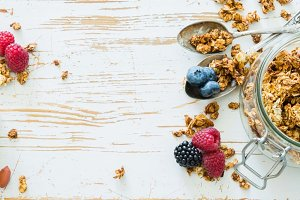 Granola with berries on white wood background
