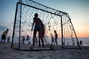 Football on the beach at sunset