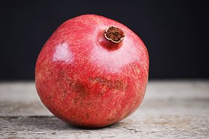 Whole pomegranate on a wooden table. Background fades from brown to black with copy space