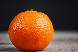Fresh juicy tangerine on black background