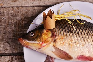 crucian carp  With a crown on wooden table. creative concept. King of fish