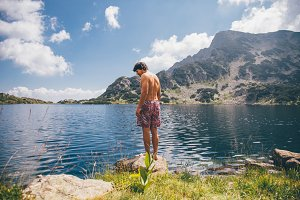 Young man at a mountain lake