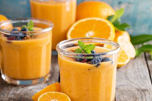 Orange and mango smoothie with granola and berries