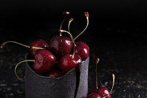 Fresh sweet cherries in black cup