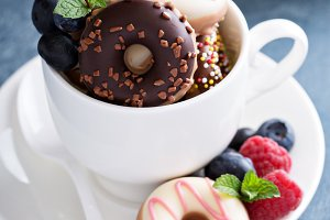 Little colorful donuts in white cup