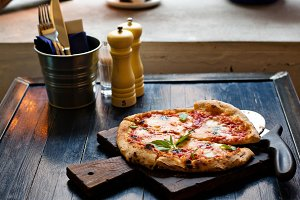 Pizza Margherita freshly baked on a table in cafe