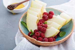 Melon slices served with raspberry and honey