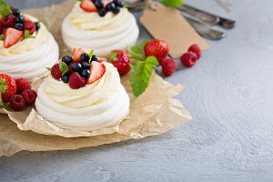 Pavlova cakes with cream and fresh berries