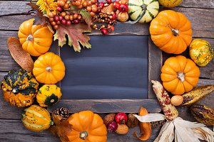 Variety of colorful decorative pumpkins around a chalkboard