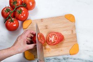 Hand slicing tomatoes
