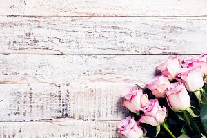 wooden background with bouquet of pink roses