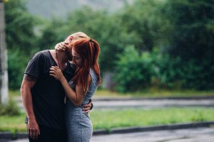 beautiful couple hugging in the rain