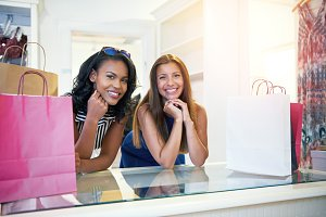 Two happy young women waiting to pay in a store