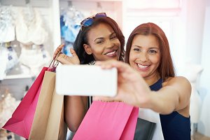 Happy young women taking a selfie while shopping
