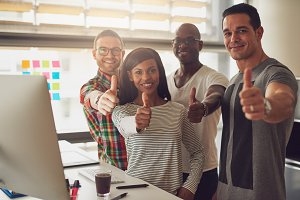 Four business partners with thumbs up