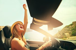 Excited woman driving her car with raised fist