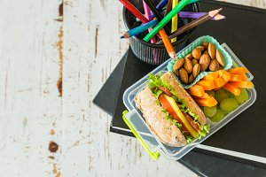 School lunch box with books and pencils in front of black board