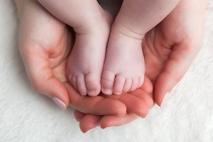 Baby feet in mother's hands.