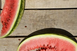 Ripe watermelons on wicker tray on table on wooden background