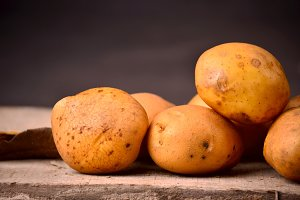 Fresh organic young potatoes on wooden black background